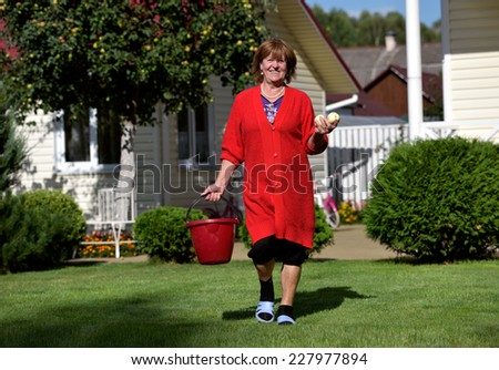 Portrait of senior woman with apples in the sunny garden