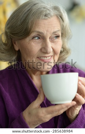 Portrait of senior woman with cup of coffee - stock photo