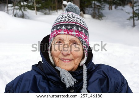 Portrait of senior woman with wool hat enjoying cold winter - stock photo
