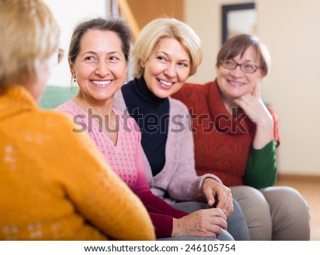 Portrait of senior women having discussion indoor and laughing. Focus on one - stock photo