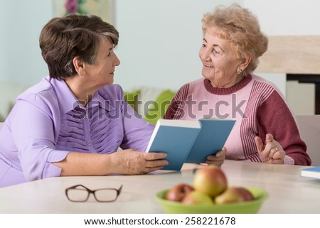 Portrait of senior women sitting at the table - stock photo