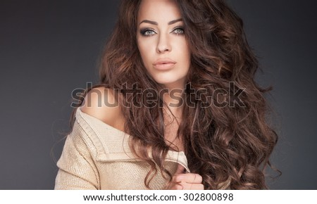 Portrait of sensual beautiful brunette woman with long curly hair and perfect makeup. Studio shot. - stock photo