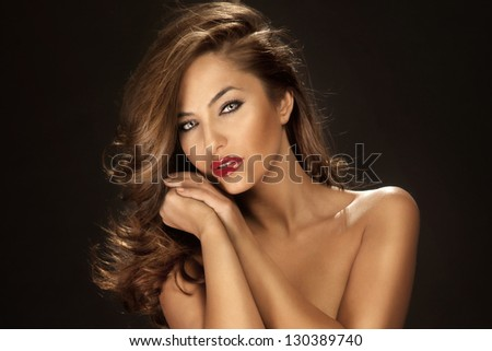 Portrait of sensual beauty with long curly hair wearing red lipstick and beautifyl makeup. - stock photo