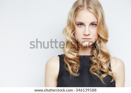 Portrait of sensual blond woman with curly hair over light grey background. - stock photo