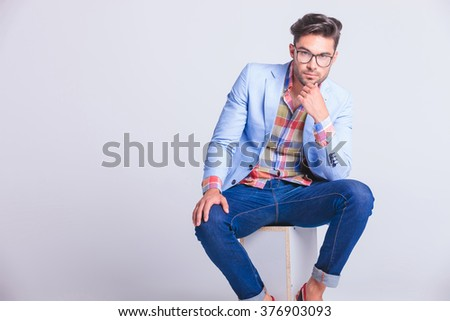 portrait of sensual casual man wearing glasses and jeans seated and thinking while looking at the camera in studio background