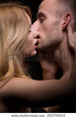 Portrait of sensual couple kissing - black backround