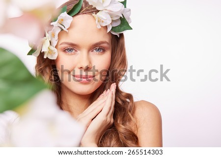 Portrait of sensual girl in floral wreath looking at camera