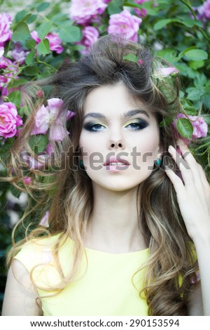 Portrait of sensual thoughtful young blonde woman with bright makeup and curly hair with lush bush of pink rose, vertical picture - stock photo