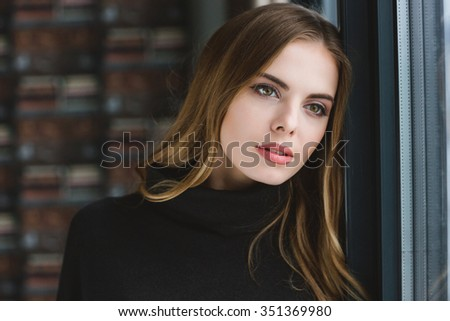 Portrait of sensual thoughtful young female dreaming near the window - stock photo