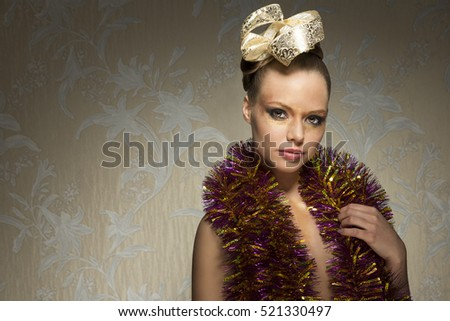 portrait of sensual woman with sparkly creative look. She posing with golden make-up, ribbon in the hair-style and tinsel on breast