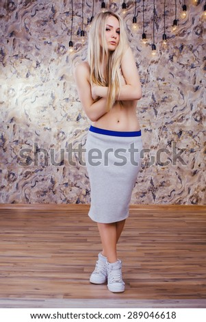 Portrait of sensual young blonde girl. With perfect slim body. In fashionable skirt. Posing in studio. - stock photo