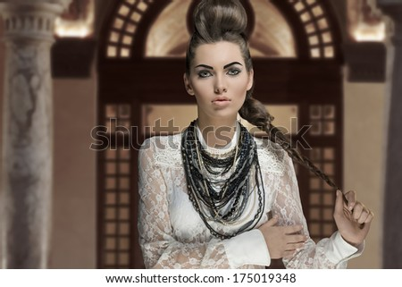 portrait of sensual young brunette woman with creative fashion style and cute hairdo and make-up. Wearing white lace shirt and a lot of necklaces