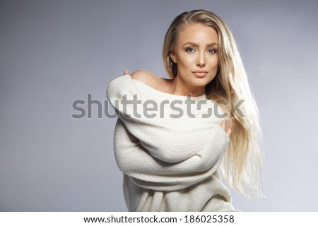 Portrait of sensual young woman wearing oversized sweater looking at camera. Beautiful caucasian female fashion model posing on grey background with copyspace. - stock photo