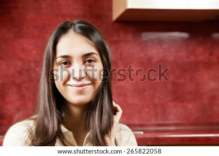 Portrait of serene brunette against red wall - stock photo