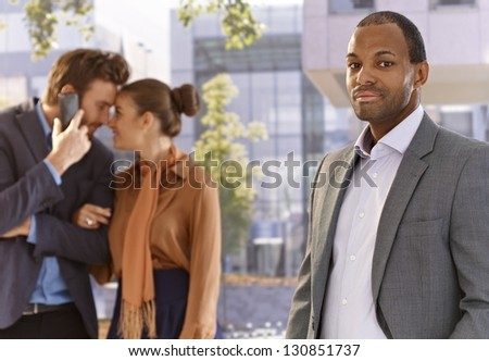 Portrait of serious afro businessman front of skyscrapers, young couple at background.