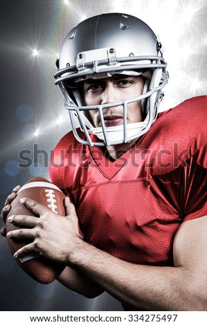 Portrait of serious American football player holding ball against spotlights