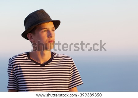 Portrait of serious and pensive young man on sunset sky background, outdoor, Italy. - stock photo