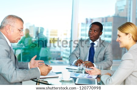 Portrait of serious boss looking into his notepad during explanation with pretty secretary looking at him - stock photo