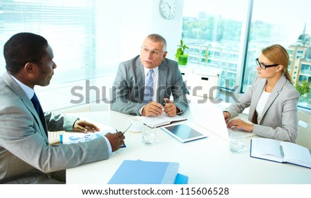 Portrait of serious boss talking and his employees listening to him - stock photo