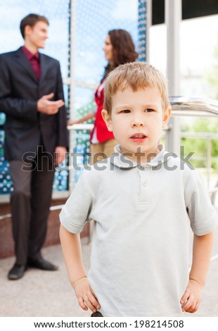 Portrait of serious boy with his parents behind - stock photo