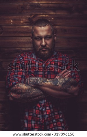 Portrait of serious brutal man with beard and tattooes. Crossed arms. - stock photo