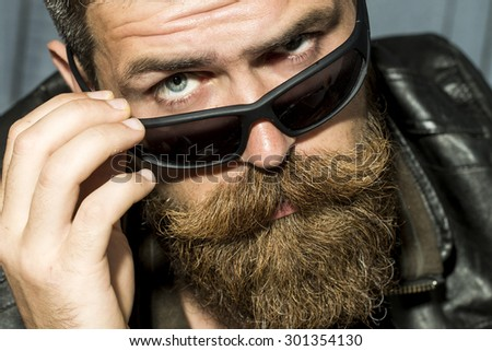 Portrait of serious brutal unshaved male biker with long beard and moustache in brown leather jacket and black sunglasses looking forward closeup, horizontal picture - stock photo