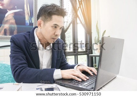 Portrait of serious business man working on computer