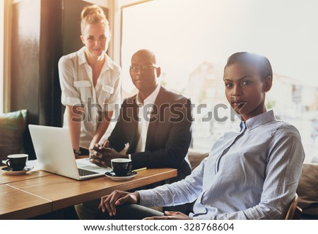 Portrait of serious business people, multi ethnic, sitting at a coffee shop working - stock photo