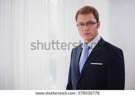 Portrait of serious businessman, dark blue suit with a blue tie and glasses, standing in office in front of windows. - stock photo