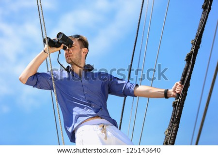Portrait of serious businessman looking through binoculars on the background of blue sky