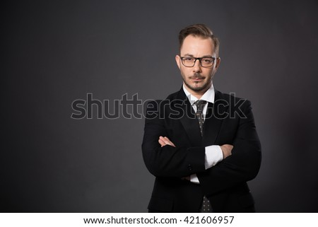 Portrait of serious businessman posing with his arms crossed or folded in studio. Handsome bearded man in glasses looking at camera.