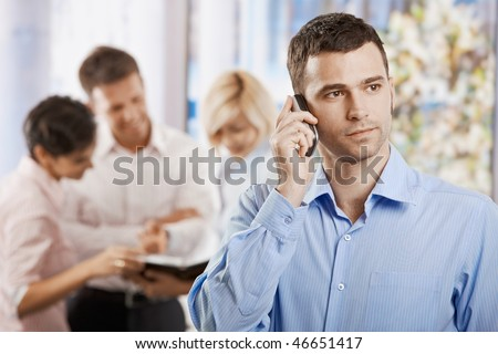 Portrait of serious businessman talking on mobile phone in office. - stock photo
