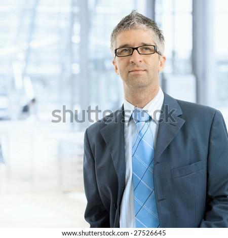 Portrait of serious businessman wearing gray suit with blue tie and glasses, standing in office lobby, in front of windows. - stock photo