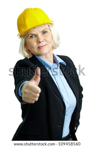 Portrait of serious businesswoman in helmet showing thumb up and looking at camera - stock photo