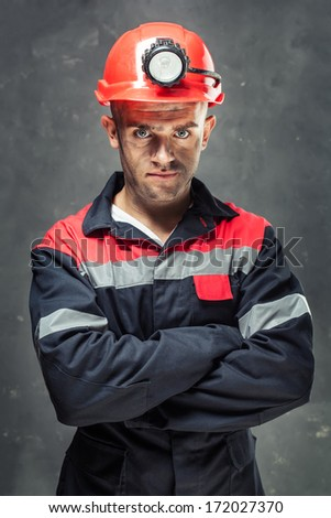 Portrait of serious coal miner with his arms crossed against a dark background - stock photo