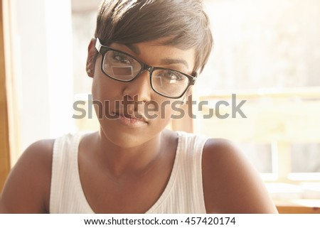 Portrait of serious confident African female freelancer wearing glasses looking at the camera with thoughtful concentrated expression. Attractive woman manager sitting at the desk after hard work day - stock photo