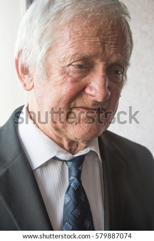 Portrait of serious  elderly man of eighty years looking somewhere and  thinks about something.