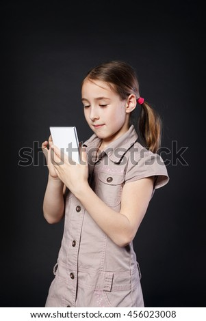 Portrait of serious girl dial on touch screen of mobile phone at black background. Female child using internet in cell phone. New generation devices, communication - stock photo