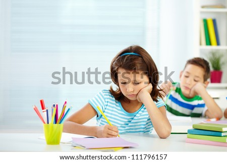 Portrait of serious girl drawing at workplace with her schoolmate on background