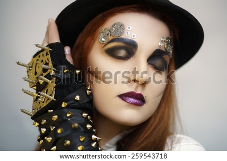 Portrait of serious golden woman alien with mechanic parts and small clock details decoration, beautiful face, black smoky eyes, thinking, dark lips, sleeve with studs, new steam punk conceptual art - stock photo