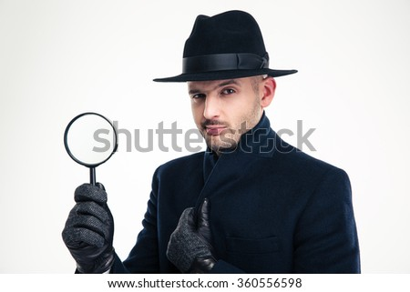 Portrait of serious handsome detective in black coat, hat and gloves holding magnifying glass over white background - stock photo