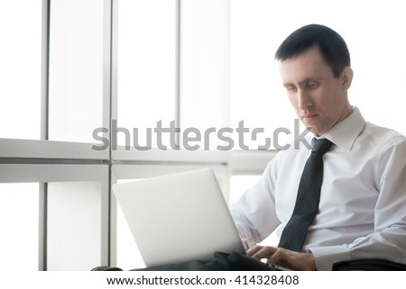 Portrait of serious handsome young business man working on laptop computer. Caucasian businessperson in formal wear during his workday. Office worker focusing on work. Copy space. - stock photo