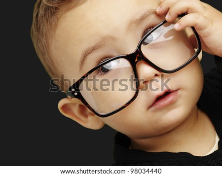 portrait of serious kid wearing glasses and doing a gesture over - stock photo