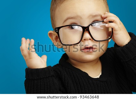 portrait of serious kid wearing glasses and doing a gesture over blue background - stock photo