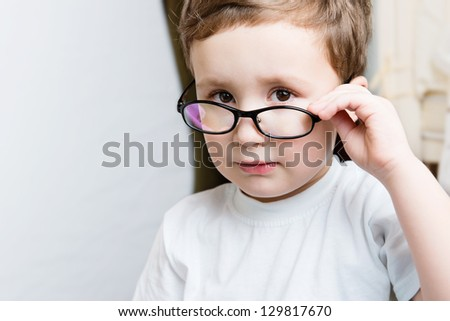 Portrait of serious kid wearing glasses and looking at camera