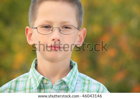 portrait of serious little boy with glasses in early fall park. - stock photo