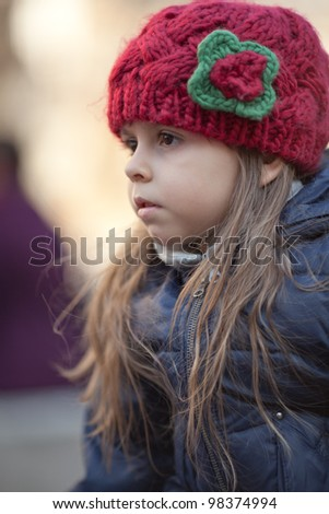 Portrait of serious little girl in red knitted hat