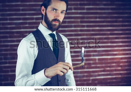 Portrait of serious man holding razor against brick wall
