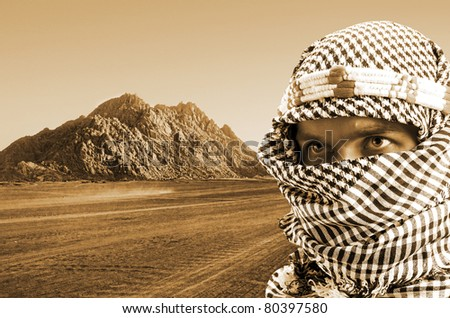 Portrait of serious middle eastern man in desert at sunset. Sepia toned