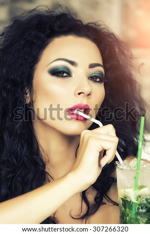 Portrait of serious pretty brunette woman with curly hair and bright makeup with alcoholic mojito cocktail from mint soda light rum ice cubes and lime with straw, vertical picture - stock photo